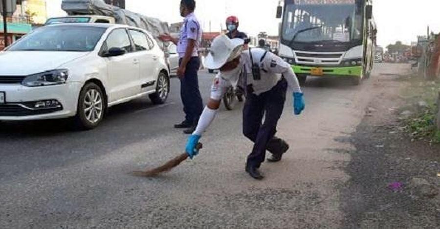 ट्रैफिक पुलिस वाले यह सुनिश्चित करने के लिए सड़क पर सफाई करते हैं कि मोटर चालक ढीले बजरी पर फिसले नहीं [वीडियो]